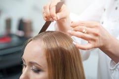 Stilist die het hairparting voor een vrouwelijke bezoeker van schoonheidssalon doen royalty-vrije stock afbeeldingen