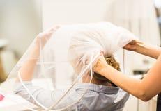 Stilist die het kapsel en de bruidssluier van een bruid vastmaken vóór het huwelijk royalty-vrije stock fotografie