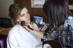 Stilist die jonge mooie bruid voorbereiden op huwelijksdag royalty-vrije stock foto