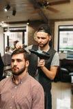 Stilist die modern kapsel voor de jonge mens maakt royalty-vrije stock foto's