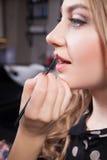 Stilist die professionele make-up van jonge vrouw doen royalty-vrije stock foto's