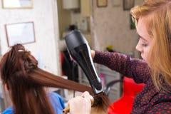 Stilist die Slagdroger op Haar van Cliënt met behulp van stock fotografie