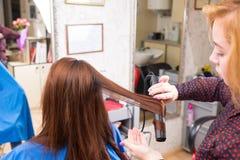 Stilist die Vlak Ijzer op Haar van Donkerbruine Cliënt gebruiken royalty-vrije stock afbeeldingen