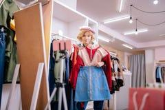 Stilist die zich voor spiegel in toonzaal bevinden die nieuwe uitrustingen kiezen royalty-vrije stock foto's