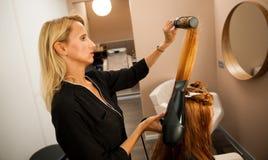 Stilist drogend haar van een vrouwelijke cliënt bij de schoonheidssalon - hai stock afbeelding