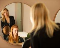 Stilist drogend haar van een vrouwelijke cliënt bij de schoonheidssalon - hai stock fotografie