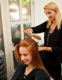 Stilist drogend haar van een vrouwelijke cliënt bij de schoonheidssalon - hai stock foto's