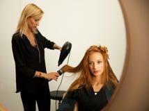 Stilist drogend haar van een vrouwelijke cliënt bij de schoonheidssalon - hai royalty-vrije stock afbeeldingen