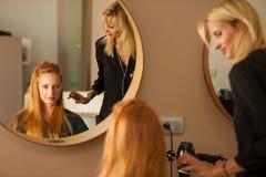 Stilist drogend haar van een vrouwelijke cliënt bij de schoonheidssalon - hai royalty-vrije stock foto's