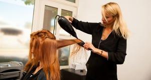 Stilist drogend haar van een vrouwelijke cliënt bij de schoonheidssalon - hai royalty-vrije stock afbeelding