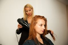 Stilist drogend haar van een vrouwelijke cliënt bij de schoonheidssalon - hai stock afbeeldingen