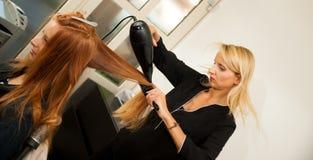Stilist drogend haar van een vrouwelijke cliënt bij de schoonheidssalon - hai royalty-vrije stock fotografie