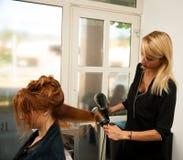 Stilist drogend haar van een vrouwelijke cliënt bij de schoonheidssalon - hai stock foto