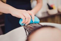 stilist het borstelen vrouwenhaar in salonpool royalty-vrije stock fotografie