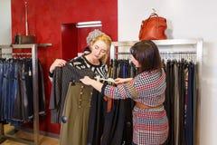 Stilist het helpen kiest kleren voor de klant royalty-vrije stock afbeelding