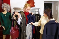 Stilist het helpen kiest kleren voor de klant stock fotografie