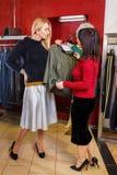 Stilist het helpen kiest kleren voor de klant stock foto