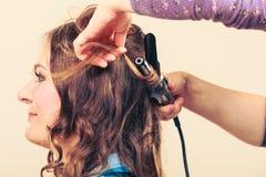 Stilist krullend haar voor jonge vrouw royalty-vrije stock afbeelding