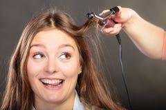 Stilist krullend haar voor jonge vrouw stock foto