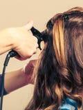 Stilist krullend haar voor jonge vrouw royalty-vrije stock foto