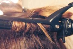 Stilist krullend haar voor jonge vrouw royalty-vrije stock fotografie