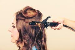 Stilist krullend haar voor jonge vrouw stock fotografie