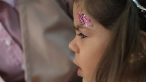 Stilist macht Berufsmake-up vom kleinen Mädchen mit stilvollen Scheinen auf Braue im Schönheitswohnzimmer stock footage