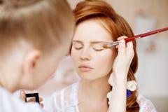 Stilist macht Make-upbraut vor der Hochzeit Lizenzfreies Stockfoto