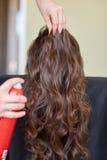 Stilist met haarlak die kapsel maken bij salon royalty-vrije stock fotografie