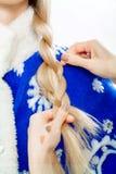 Stilist ` s übergibt Bortenzopf für Schnee-Mädchen Stockfoto