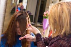 Stilist Scherpe Klappen voor Cliënt met Bruin Haar royalty-vrije stock afbeelding