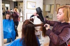Stilist-Schlag-trocknendes Haar des Kunden im Salon Lizenzfreies Stockbild
