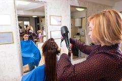 Stilist-trocknendes Haar des Brunette-Kunden im Salon Lizenzfreies Stockbild