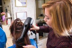 Stilist-trocknendes Haar des Brunette-Kunden im Salon Lizenzfreie Stockfotografie