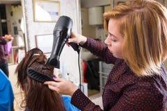 Stilist-trocknendes Haar des Brunette-Kunden im Salon Stockfotos