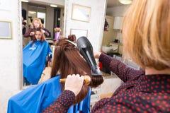 Stilist-trocknendes Haar des Brunette-Kunden im Salon Lizenzfreie Stockfotos