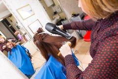 Stilist-trocknendes Haar des Brunette-Kunden im Salon Stockbild