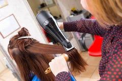Stilist-trocknendes Haar des Brunette-Kunden im Salon Lizenzfreie Stockbilder