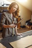 Stilista abbastanza messo a fuoco della giovane donna che taglia tessuto bianco in studio fotografia stock