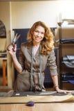 Stilista abbastanza messo a fuoco della giovane donna che taglia tessuto grigio in studio fotografia stock