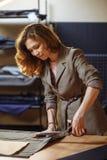 Stilista abbastanza messo a fuoco della giovane donna che taglia tessuto grigio in studio immagini stock