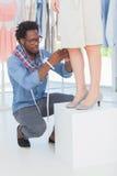 Stilista attraente che regola un vestito fotografia stock libera da diritti