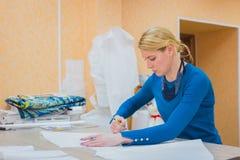 Stilista che lavora con il modello di nuova raccolta di alte mode Fotografia Stock