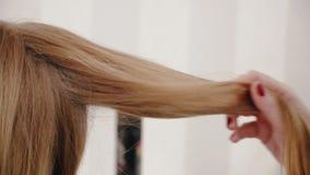 Stilista che pettina capelli lunghi alla ragazza bionda archivi video