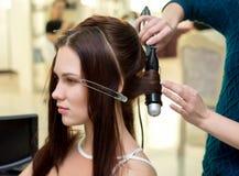 Stilista di capelli che fa i ricci alla donna castana Lavoro del parrucchiere fotografia stock libera da diritti