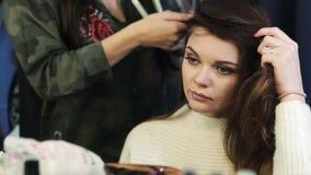 Stilista di capelli che fa i ricci alla donna castana Parrucchiere che lavora con i bei capelli della donna nel salone di lavoro  archivi video