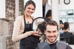 Stilista di capelli grazioso che mostra ad uomo nuovo taglio di capelli fotografie stock