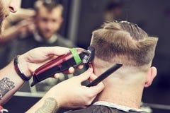 Stilista di capelli o del barbiere sul lavoro Capelli di taglio del parrucchiere del cliente Immagine Stock