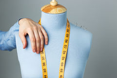 Stilista e manichino blu del sarto con la foto alta vicina di misurazione del nastro Fotografie Stock Libere da Diritti