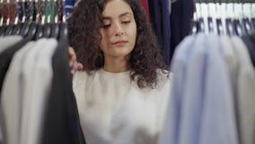 Stilistfrau überprüft neue Kleidungssammlung im Geschäft, bewegliche Aufhänger stock footage